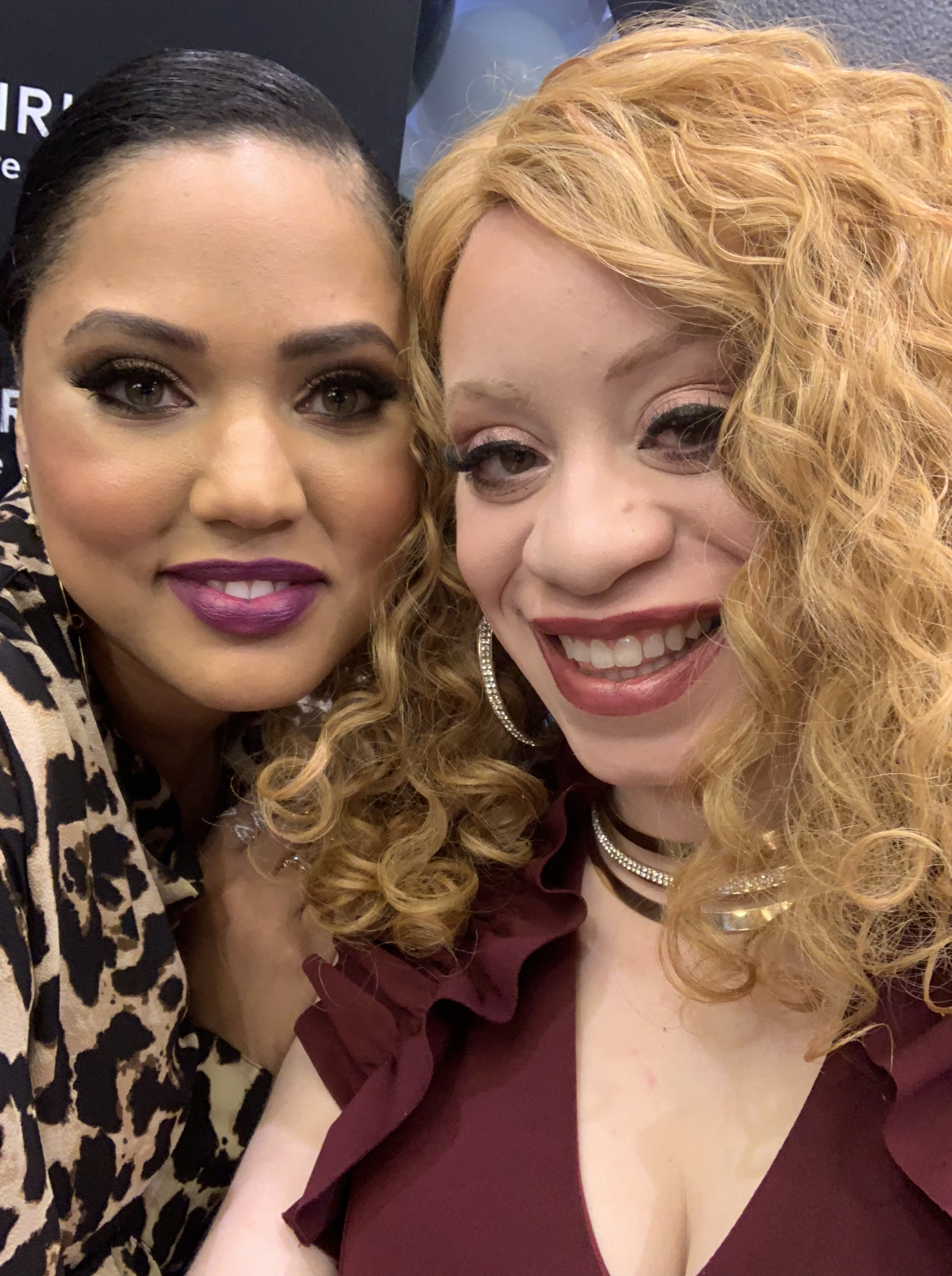 Ayesha Curry is wearing bright fuchsia lipstick and leopard print top. She is pictured next to J Renée.