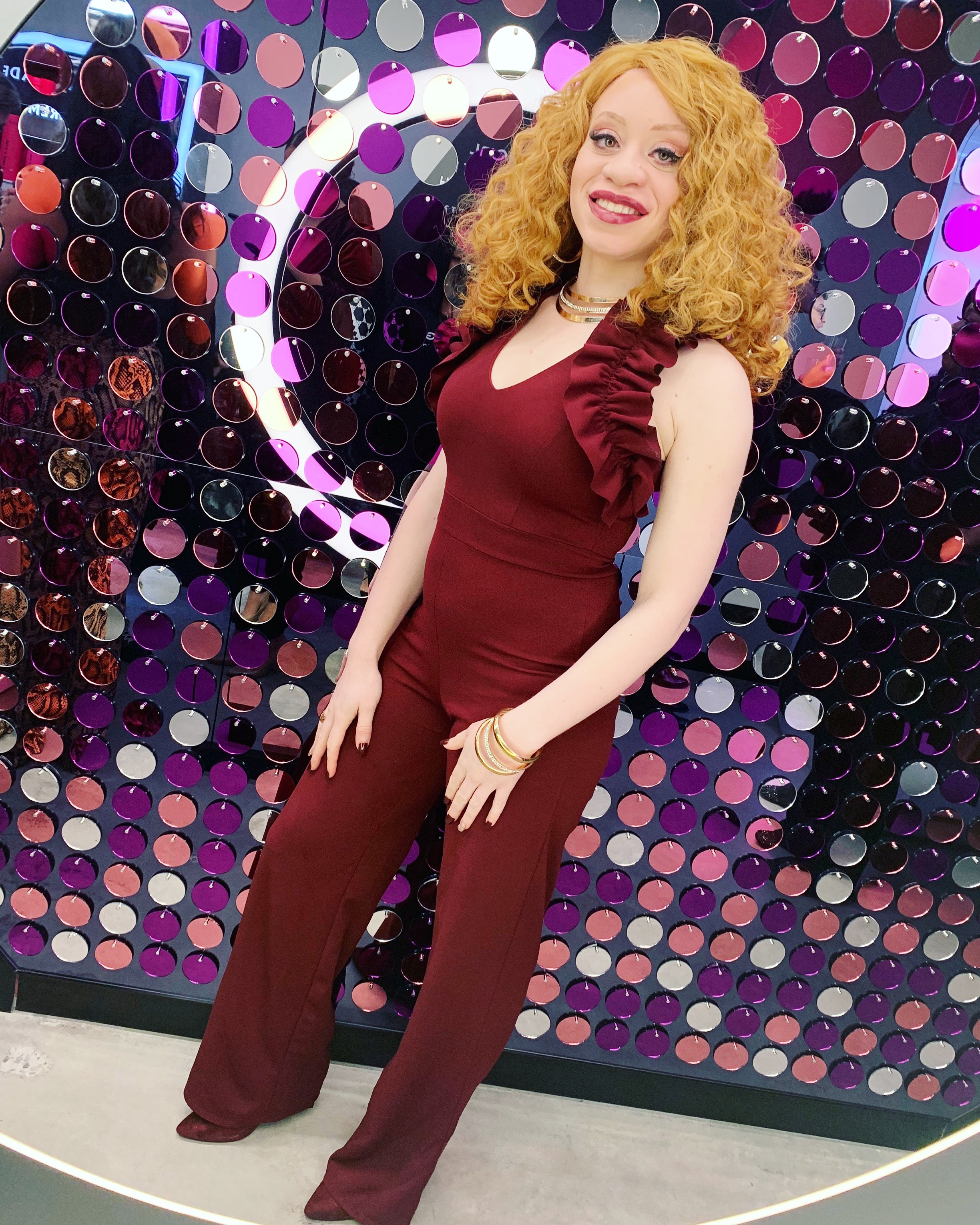 J Renée is wearing a burgundy romper and matching boots with gold and rhinestone jewelry.